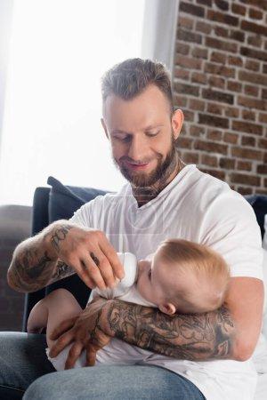 młody wytatuowany mężczyzna karmienie niemowlę chłopiec z butelki dla dzieci w domu