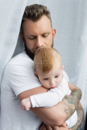 Photo for Young tattooed man in white t-shirt holding infant son in hands with closed eyes - Royalty Free Image