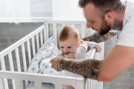 Photo pour Jeune père soutien enfant fils debout dans la crèche avec la main dans la bouche - image libre de droit
