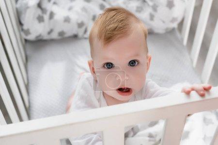 Photo pour Vue aérienne de bébé garçon regardant la caméra tout en étant debout dans le berceau avec la bouche ouverte - image libre de droit