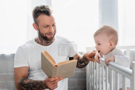 Photo pour Jeune tatoué homme lecture livre à excité bébé garçon debout dans la crèche - image libre de droit