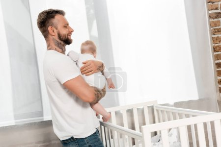 Photo for Young father holding infant boy while standing at crib near window - Royalty Free Image