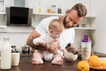 infant boy touching bowl with breakfast while sitting on kitchen table near young tattooed father