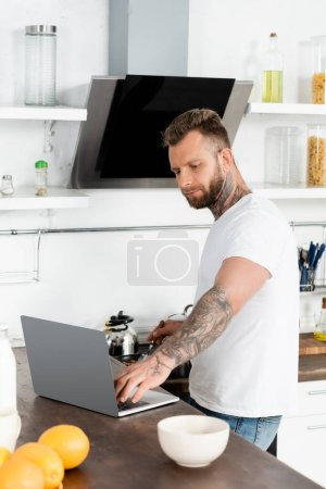 young, bearded freelancer in white t-shirt using laptop near oranges and bowl in kitchen