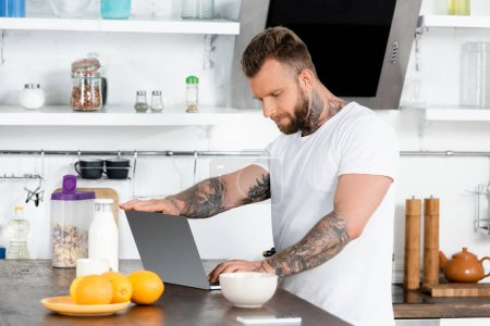 Photo for Tattooed freelancer in white t-shirt using laptop near bottle of milk, bowl and oranges in kitchen - Royalty Free Image