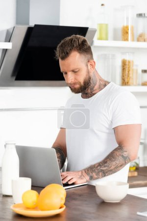 Photo for Young tattooed freelancer using laptop near bowl, oranges, and bottle of milk in kitchen - Royalty Free Image
