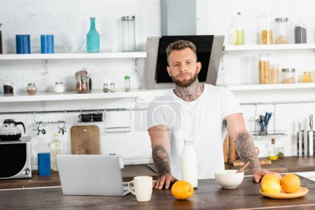 Photo for Bearded, tattooed blogger in white t-shirt looking at camera near breakfast and laptop in kitchen - Royalty Free Image