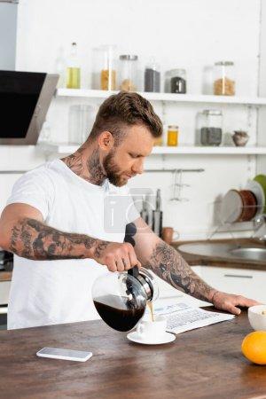 Photo pour Homme tatoué en t-shirt blanc lecture journal et verser du café près du téléphone mobile sur la table de cuisine - image libre de droit