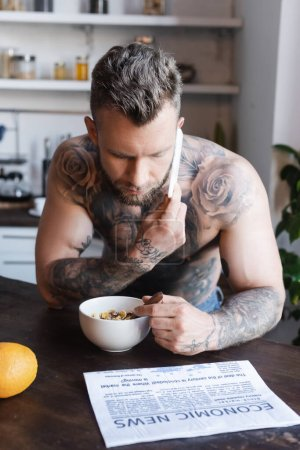 Photo for Shirtless tattooed man talking on smartphone during breakfast near newspaper - Royalty Free Image