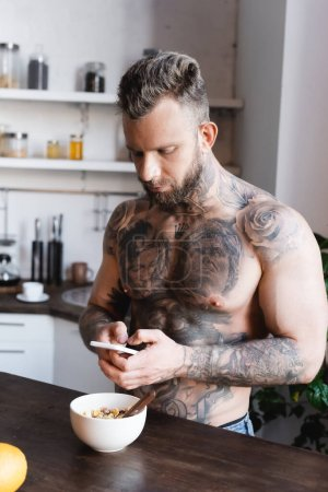 Photo for Tattooed, muscular man using laptop while standing near bowl with breakfast in kitchen - Royalty Free Image