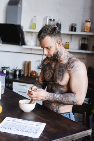 young tattooed man chatting on smartphone while standing near bowl with breakfast