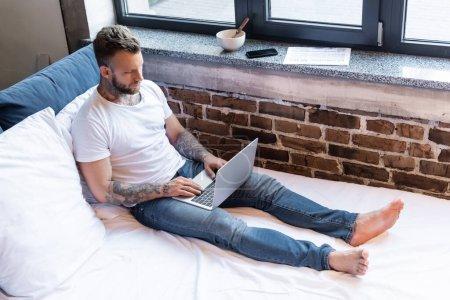 pigiste tatoué en jeans et t-shirt blanc à l'aide d'un ordinateur portable sur le lit près du journal, smartphone et bol sur le rebord de la fenêtre