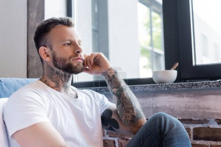 serious tattooed man sitting near window at home and looking away
