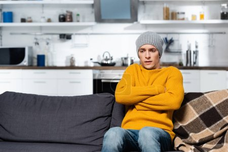 Photo pour Homme frissonnant en pull tricoté et chapeau assis sur le canapé avec les bras croisés dans la cuisine froide - image libre de droit