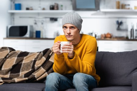 cold man in knitted sweater and hat looking at camera while holding cup of warm tea in kitchen