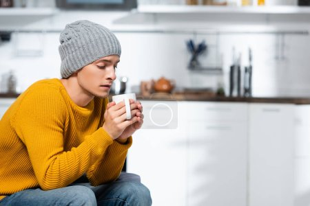 young man in knitted sweater and hat holding cup of warm tea in kitchen