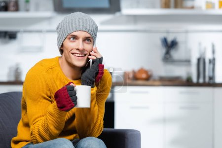 Photo pour Joyful man in fingerless gloves and knitted hat talking on cellphone while holding cup of warm drink - image libre de droit