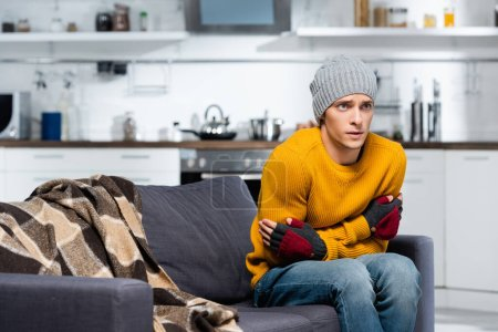 young man in warm hat and fingerless gloves hugging himself while sitting on sofa in cold kitchen