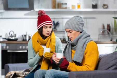 Photo pour Couple de congélation en bonnets tricotés, écharpes et gants tenant des tasses de boisson chaude dans la cuisine froide - image libre de droit
