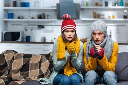 Photo pour Couple gelant dans des chapeaux chauds et des gants regardant la caméra tout en étant assis sur le canapé dans la cuisine froide - image libre de droit