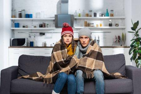 Photo pour Couple froid, enveloppé dans une couverture à carreaux, portant des chapeaux chauds, regardant la caméra tout en étant assis sur le canapé dans la cuisine - image libre de droit