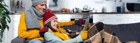 Photo pour Horizontal concept of excited couple in warm hats and gloves watching movie on laptop in cold kitchen - image libre de droit