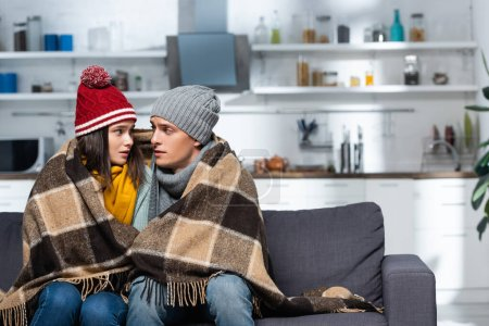 freezing couple in warm hats looking at each other while sitting under plaid blanket in cold kitchen