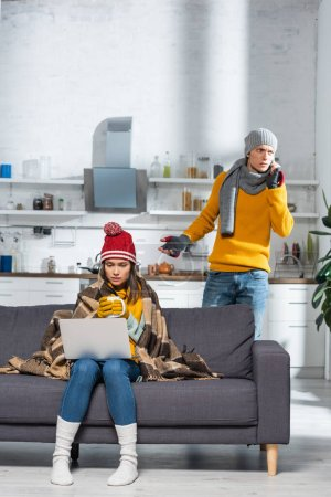 Photo pour Freezing woman sitting on sofa with laptop while worried boyfriend talking on smartphone in cold kitchen - image libre de droit