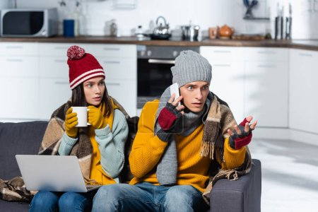 Photo pour Worried man talking on smartphone near cold woman wearing warm hat nad gloves while sitting with laptop in cold kitchen - image libre de droit