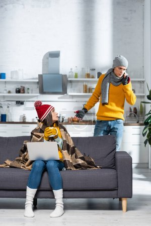 Photo pour Freezing woman in warm hat and gloves sitting on sofa with laptop while tense boyfriend talking on smartphone - image libre de droit