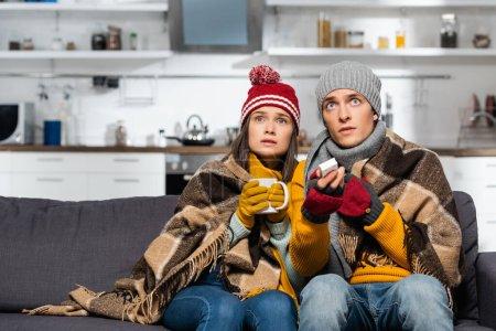 Photo pour Couple gelé dans des chapeaux chauds, enveloppé dans une couverture à carreaux, regarder la télévision tout en étant assis dans la cuisine froide - image libre de droit