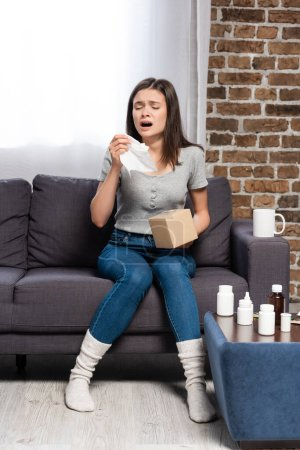Photo pour Diseased woman holding paper napkin and sneezing near cup of tea and bedside table with medicines - image libre de droit