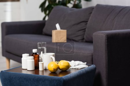 Photo pour Selective focus of medicines, fresh lemons and drinks on bedside table near grey sofa with paper napkins - image libre de droit