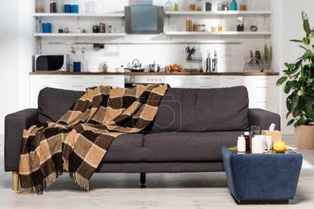 Photo pour Cuisine spacieuse avec mobilier moderne, couverture à carreaux sur canapé gris, médicaments et citrons frais sur table de chevet - image libre de droit