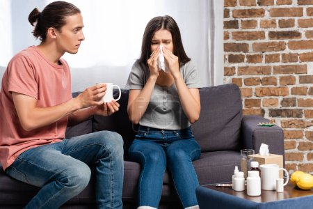 Photo pour Man holding cup of warning drink near woman sneezing in paper napkin near medicines - image libre de droit