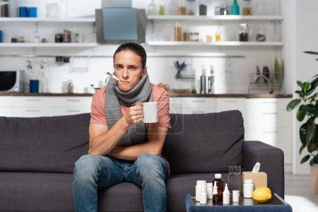 Kranker junger Mann mit Thermometer im Mund hält Becher mit wärmendem Getränk in der Küche neben Medikamenten