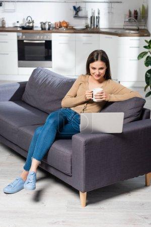 Freelancer mit einer Tasse warmen Getränks auf Couch in Küche neben Laptop