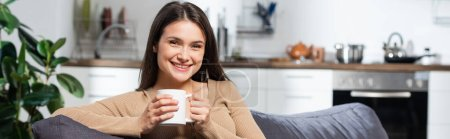 Photo for Horizontal concept of pleased woman looking at camera while sitting on couch in kitchen with cup of warming beverage - Royalty Free Image