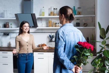 Photo pour Vue arrière de l'homme tenant bouquet de roses derrière le dos près de femme excitée debout avec les bras ouverts dans la cuisine - image libre de droit