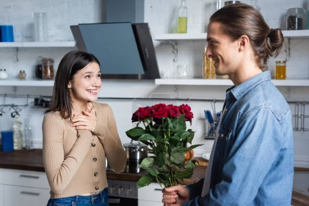 Junger Mann überreicht freudetrunkenen Frauen in Küche einen Strauß Rosen