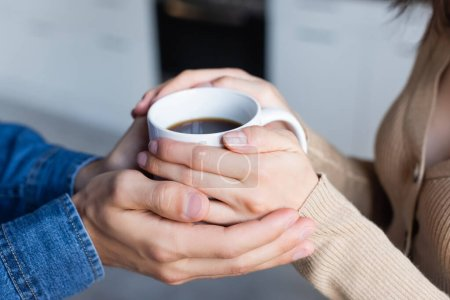 cropped view of man and woman holding cup of coffee together