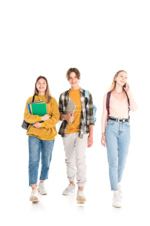 Photo for Smiling teenagers with backpacks, notebooks and smartphone walking on white background - Royalty Free Image