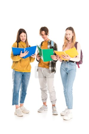 Photo for Smiling teenagers with backpacks looking at copy books on white background - Royalty Free Image