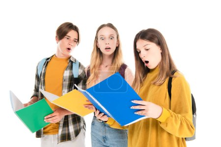 Photo for Shocked teenagers looking at notebook isolated on white - Royalty Free Image