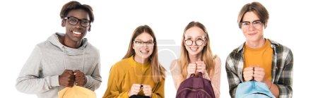 Foto de Foto panorámica de adolescentes multiétnicos en gafas con mochilas y sonrientes aislados en blanco - Imagen libre de derechos