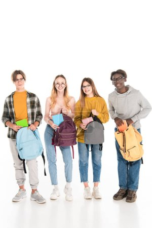 Cheerful multicultural teenagers with books and backpacks looking at camera on white background