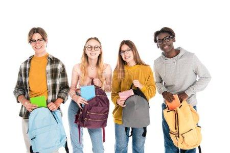 Photo pour Adolescents souriants tenant des crochets et des cahiers tout en regardant la caméra isolée sur blanc - image libre de droit