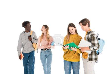 Foto de Sonrientes adolescentes multiétnicos con portátil y cuadernos hablando aislados en blanco - Imagen libre de derechos