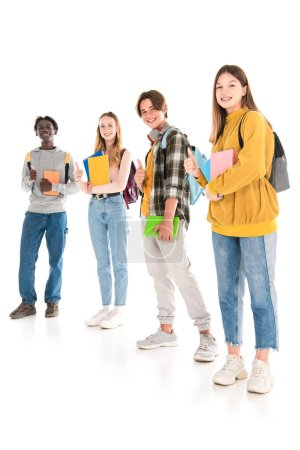 Multicultural teenagers with books and backpacks smiling at camera and showing like on white background