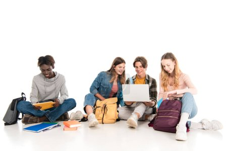 Photo for Smiling multicultural teenagers using laptop near books and backpacks on white background - Royalty Free Image